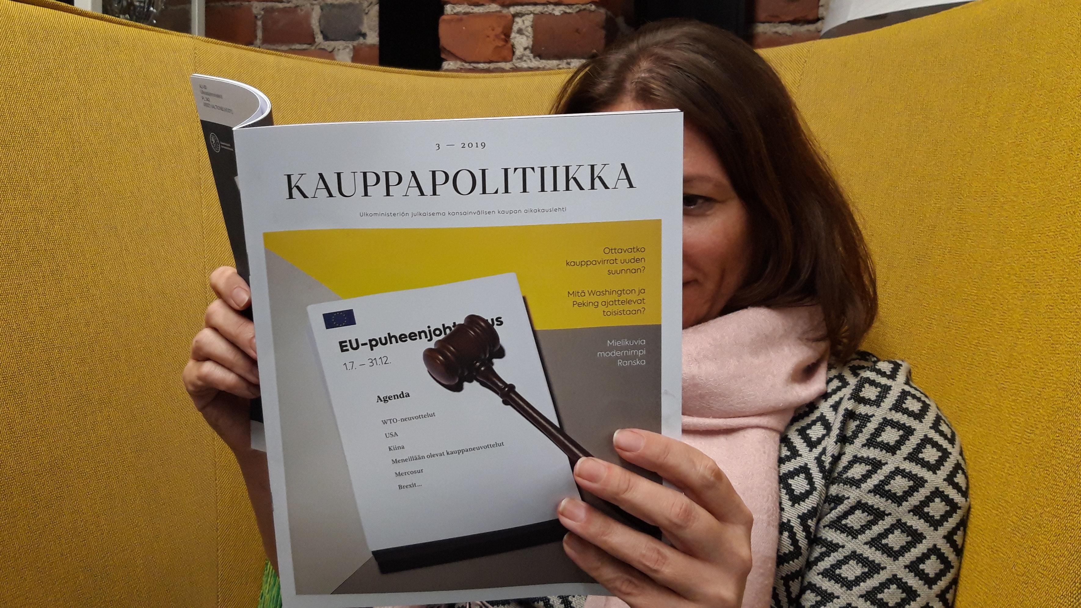Kauppapolitiikka-lehden päätoimittaja Lotta Nuotio lukemassa Kauppapolitiikka-lehteä.