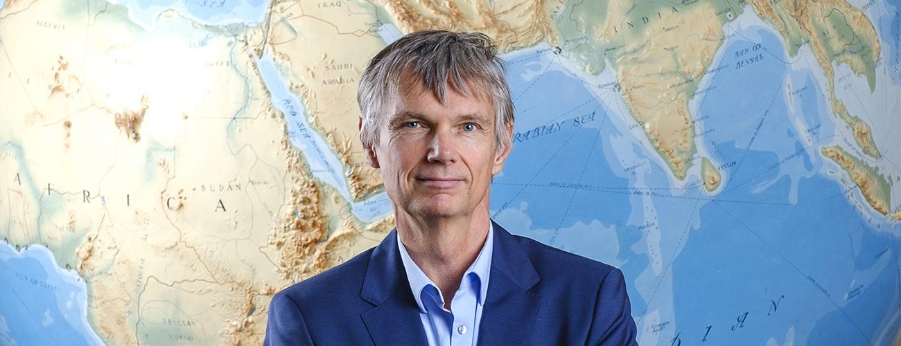 Antti Aumo maapallon kartan edessä katse kohti kameraa.