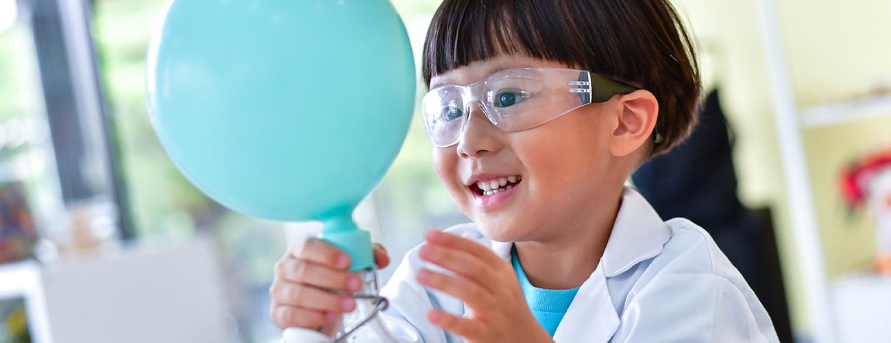 Sininen ilmapallo ja tieteellistä koetta tekevä iloinen lapsi.