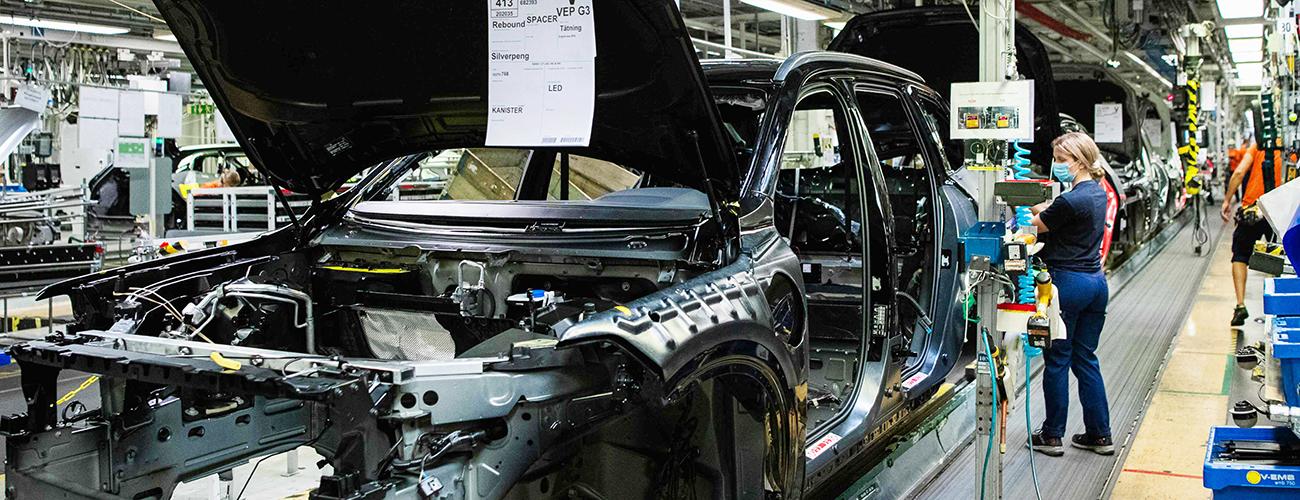 Työntekijä kokoa autoa hangityssuoja kasvoillaan Volvon tehtaalla Ruotsissa.