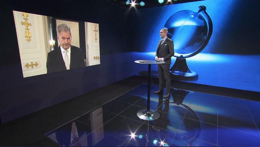 Presidentti Niinistö valkokankaalla ja Tomi Korhonen esiintymislavalla.