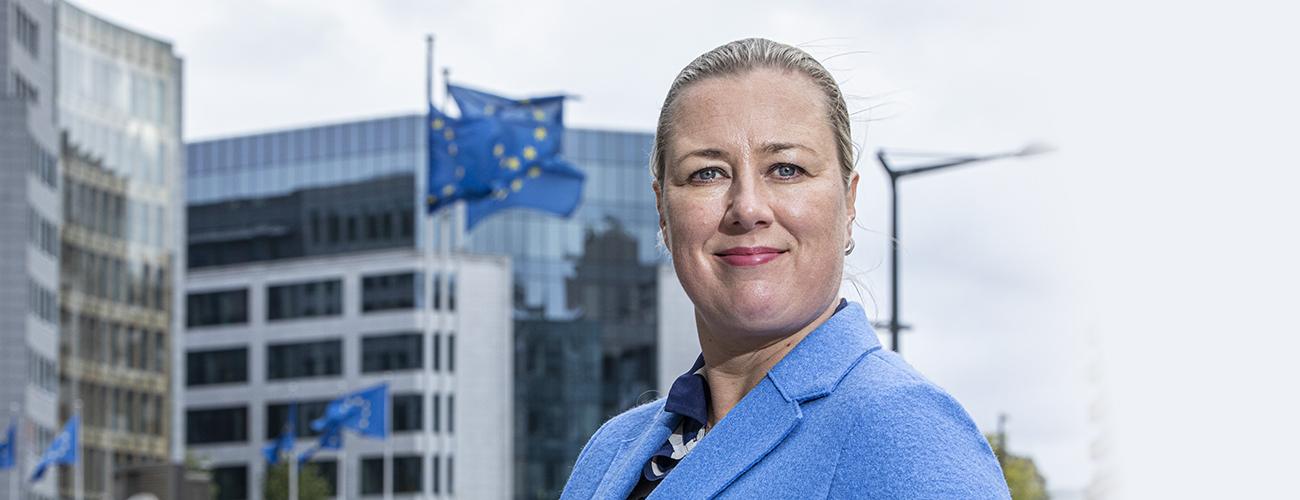 Jutta Urpilainen sinisessä jakkupuvussa Brysselissä, taustalla liehuu EU-lippuja.