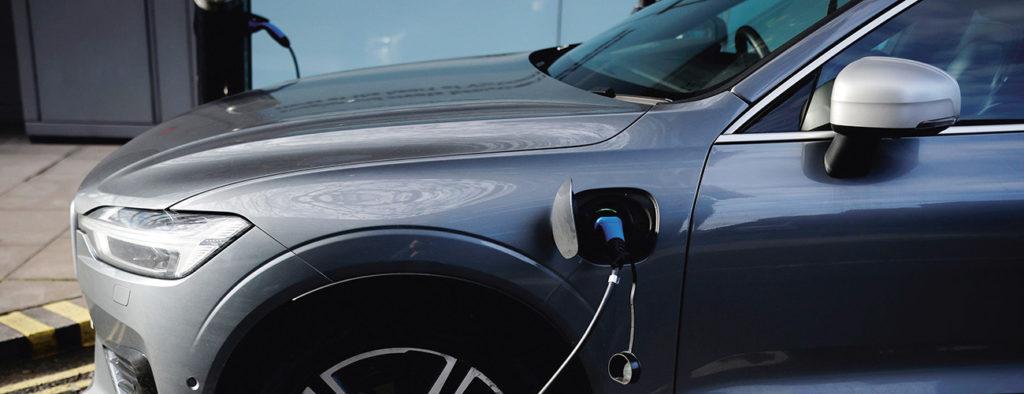 Latausjohto kiinnitettynä pysäköityyn sähköautoon.