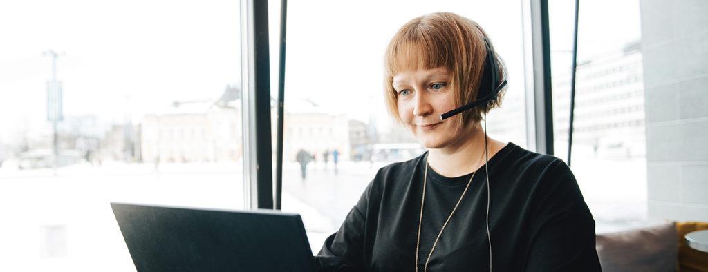 Elina Haverinen tekee etätöitä tietokoneen ääressä kuulokkeet korvilla.