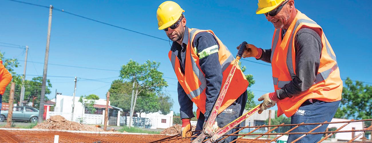 Kaksi työmiestä laikkaa raudoitusverkkoa oikeaan kokoon talon rakennustyömaalla Uruguayssa.