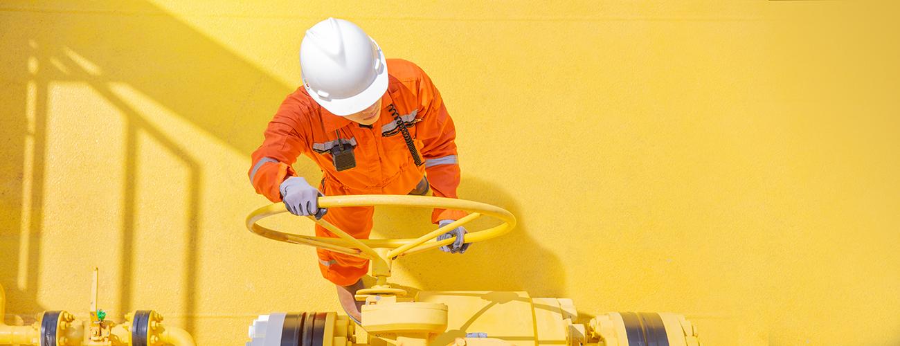Oranssipukuinen työmies kääntää ison öljyputken venttiiliä