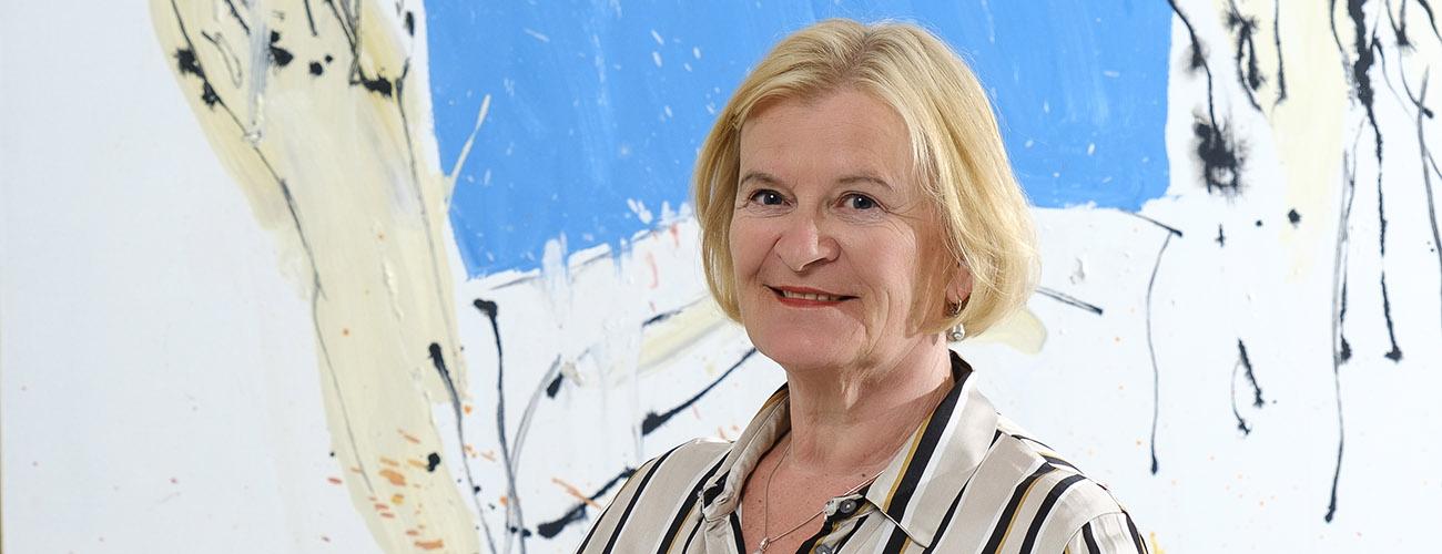 Marjo Miettinen seisoo työhoneessaan katse kohti kameraa.