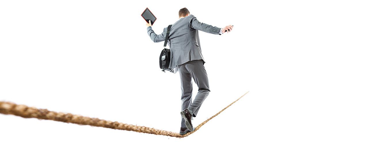 Harmaa puku päällään oleva liikemies kävelee ilmassa kireälle vedettyä narua pitkin