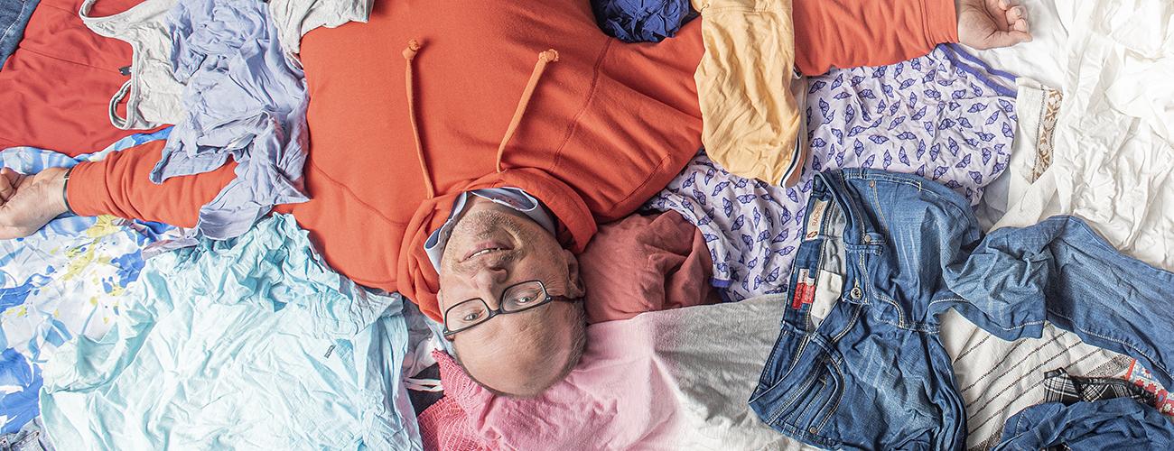 Petri Alava makaa selällään kierrätykseen menevien puhtaiden vaatteiden keskellä