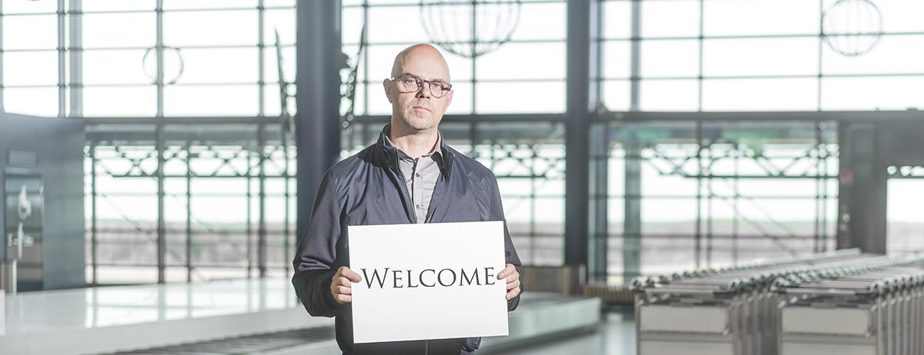 Harri Mällinen seisoo Rovaniemen lentoasemalla kädessään pahvinen kyltti, jossa lukee Welcome.