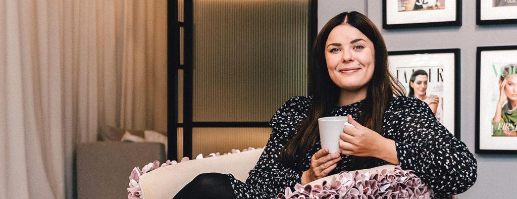 Satu Nisu istuu nojatuolissa kahvikuppi kädessään.